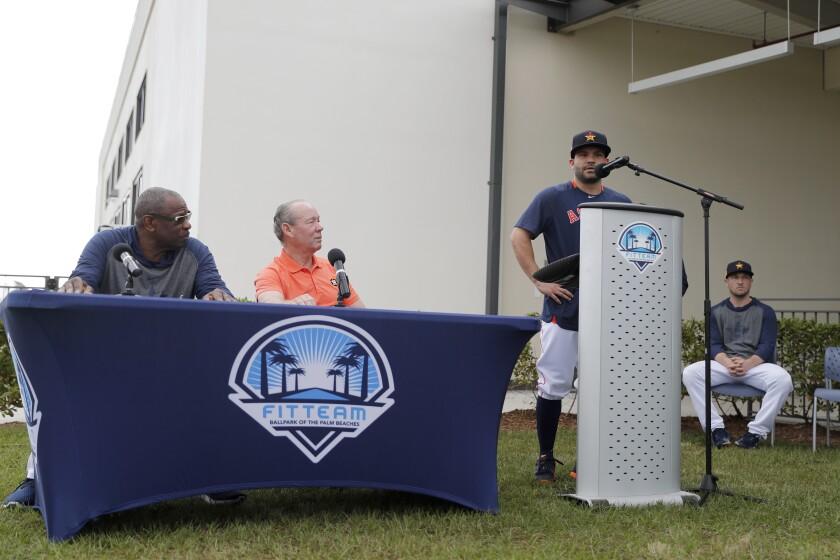 José Altuve (al micrófono) pide disculpas en nombre del equipo por el robo de señales que hicieron los Astros en las temporadas del 2017 y 2018. Lo observan el propietario del equipo Jim Crane (sentado, a la derecha) y el nuevo mánager Dusty Baker. Foto del 13 de febrero del 2020 en la concentración de pretemporada de los Astros en West Palm Beach, Florida. (AP Photo/Jeff Roberson) ;