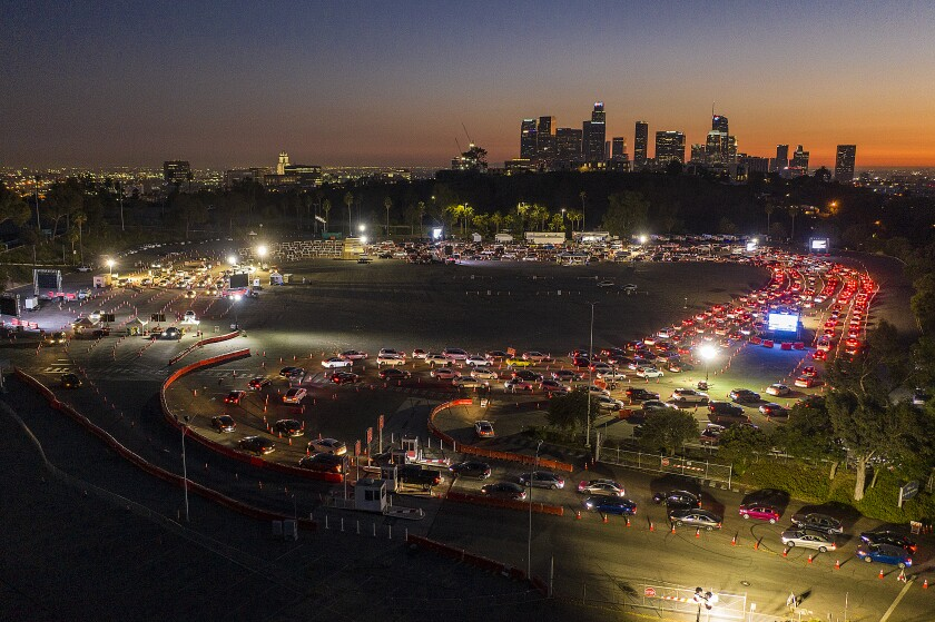 Long lines of vehicles snake through the parking lot of Dodger Stadium at night with the L.A. skyline in the background