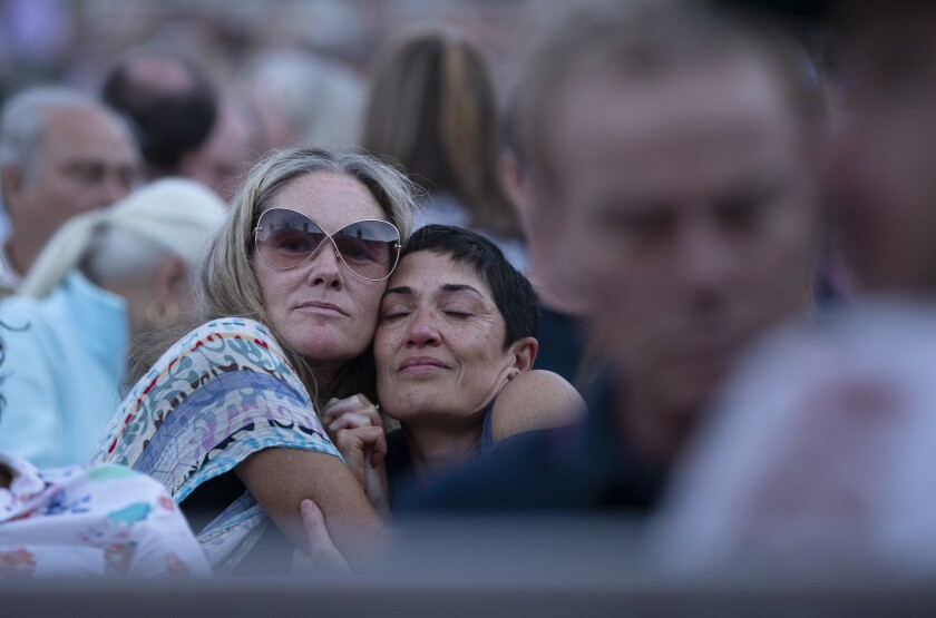 In the audience, two women share a hug.
