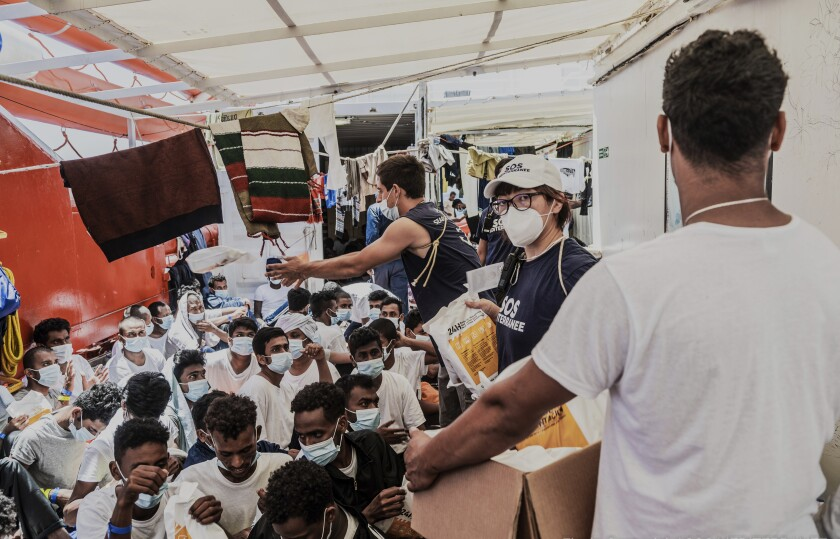 Staffers distribute food to migrants on the deck of the Ocean Viking rescue in the Mediterranean Sea on Monday, July 5, 2021. A charity rescue ship with 572 migrants aboard on Thursday, July 8, 2021 pleaded for permission to dock at some Mediterranean port as food aboard was reporting running short. Luisa Albera, search and rescue coordinator of SOS MEDITERRANEE, launched an urgent appeal from aboard the Ocean Viking. She said five requests to maritime authorities to assign a port of safety have gone unmet and tensions aboard the ship are worsening after several days in very crowded conditions. (Flavio Gasperini/SOS Mediterranee via AP)