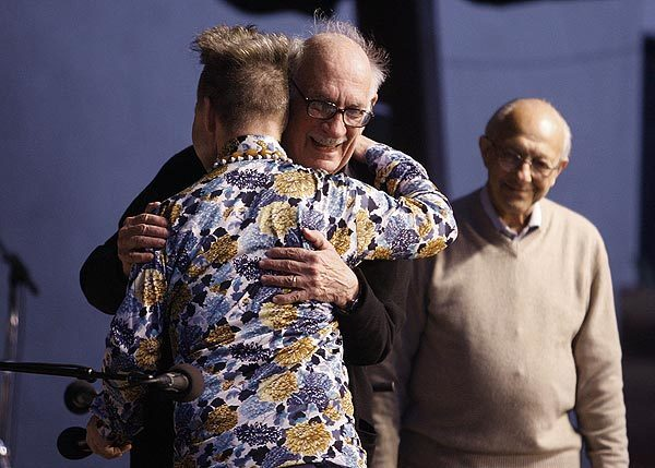 """Peter Sellars (back to camera) greets George Crumb before the start of the Ojai Music Festival concert in Ojai on June 10. At right is Gilbert Kalish. The concert featured Crumb's """"The Winds of Destiny (American Songbook IV)."""""""
