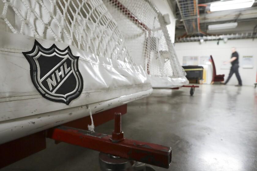 An NHL logo is shown on a hockey goal sitting on a concrete floor in a hallway.