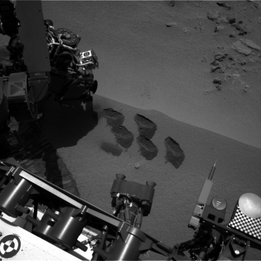 This NASA image shows marks in the Martian soil made by the rover Curiosity. It landed in August on a two-year mission to study whether Mars' environment is suitable for microbial life.