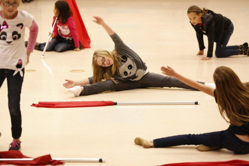 Lizzie Waddleton stretches out before a practice of a color guard routine during a discovery class at E. Curran Elementary in Murrieta. Students at E. Hale Curran Elementary had the opportunity to do after school programs that included mini color guard and scrapbooking.