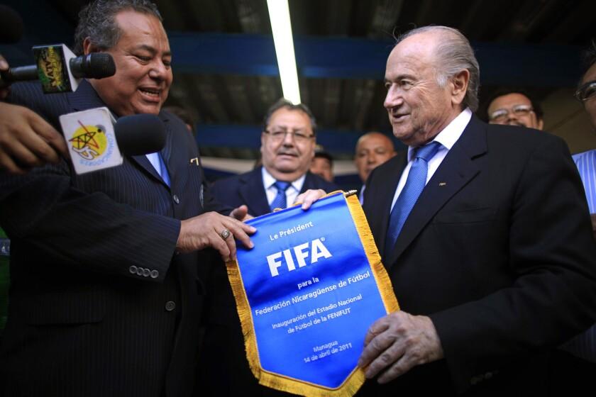 El presidente de la FIFA, Joseph Blatter, derecha, entrega una bandera al presidente de la federación de fútbol de Nicaragua, Julio Rocha, en una actividad del 14 de abril de 2011 en Managua. Rocha es uno de los dirignentes de la FIFA acusados en un caso de corrupción el 27 de mayo de 2015.