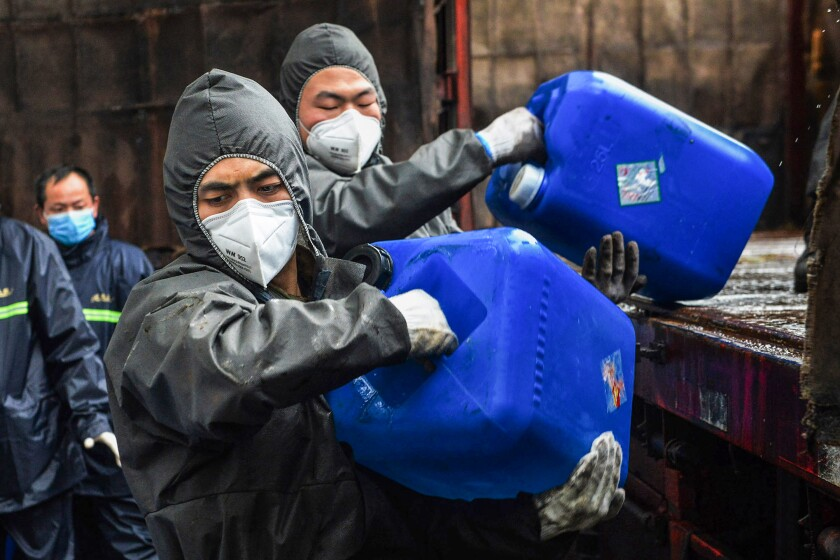 Chinese paramilitary police officers unload pails of disinfectant Feb. 12 near Xiaogan.