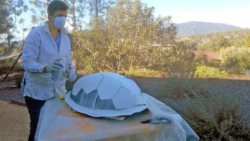Maggie Green at work in her La Canada backyard, spraying a shell to be placed on the dragon she cre
