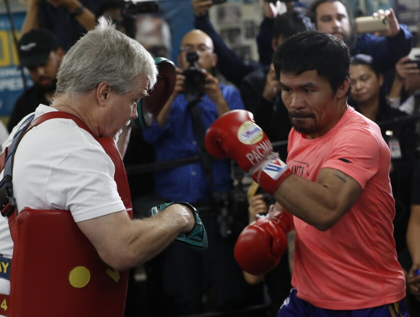 Manny Pacquiao, right, works out with trainer Freddie Roach at a boxing club in Los Angeles, Wednesday, Jan. 9, 2019. Pacquiao is scheduled to defend his WBA welterweight title against Adrien Broner on Jan. 19, 2019, in Las Vegas. (AP Photo/Damian Dovarganes)