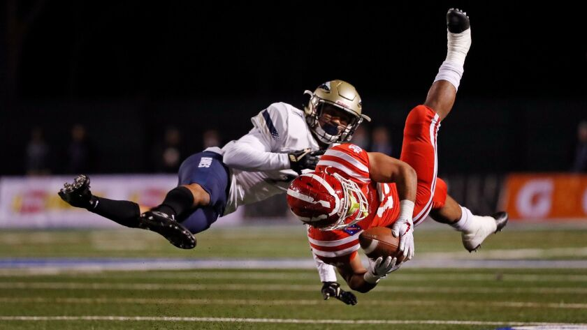 Mater Dei running back Shakobe Harper hangs onto the ball after being upended by St. John Bosco defensive back Christopher Steele during the Southern Section Division I championship game.