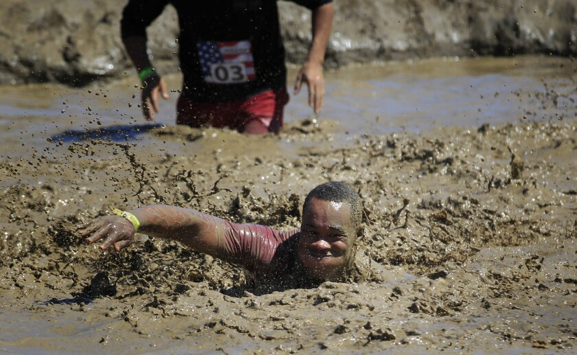 One participants attempts to swim his way through the final obstacle, the Mud Pit, before crossing the finish line on Sunday in the annual Mud Run at Camp Pendleton..