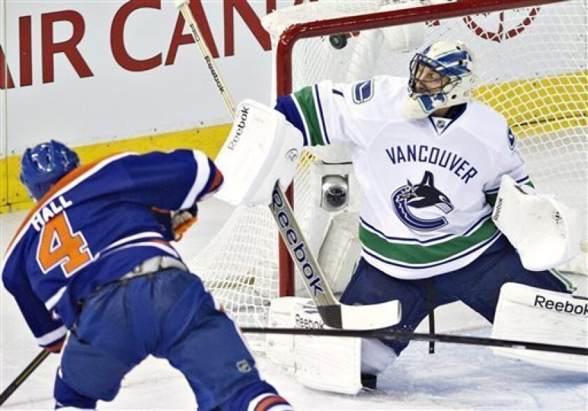 Vancouver Canucks goalie Roberto Luongo, right, is scored on by Edmonton Oilers' Taylor Hall during first-period NHL hockey game action in Edmonton, Alberta, Saturday, March 30, 2013. (AP Photo/The Canadian Press, Jason Franson)