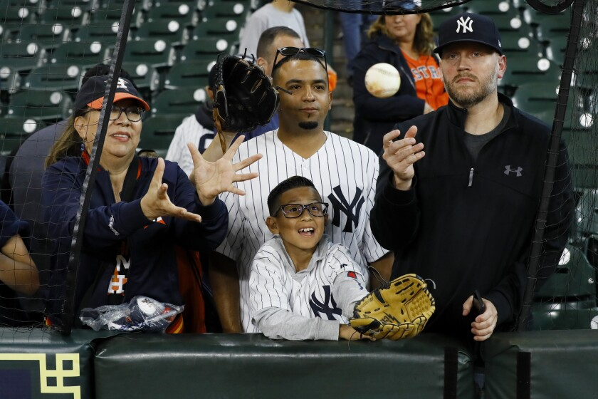 Fans wait for a ball during batting practice before Game 1 of the American League Championship Series between the Houston Astros and the New York Yankees in October.