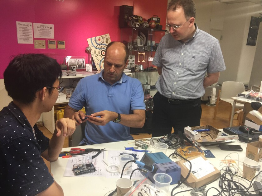 Joe Moross, center, and Pieter Franken, right, teach Kohei Matsushita how to assemble one of Safecast's Geiger counter kits at the group's Tokyo office on July 6, 2016.