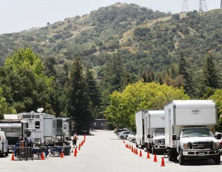 A caravan of production vehicles line up for filming a commercial.
