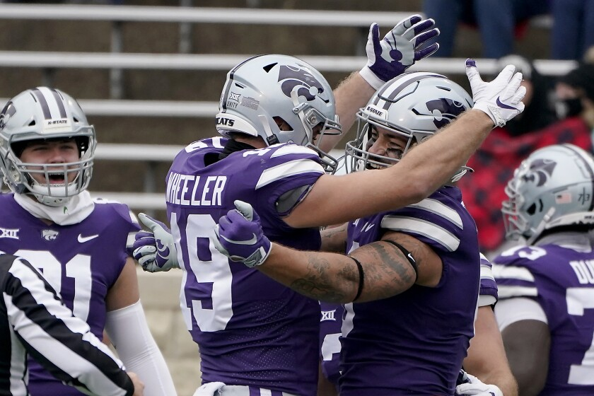 Kansas State tight end Briley Moore, right, celebrates with tight end Samuel Wheeler (19) after scoring a touchdown during the first half of an NCAA college football game against Kansas Saturday, Oct. 24, 2020, in Manhattan, Kan. (AP Photo/Charlie Riedel)