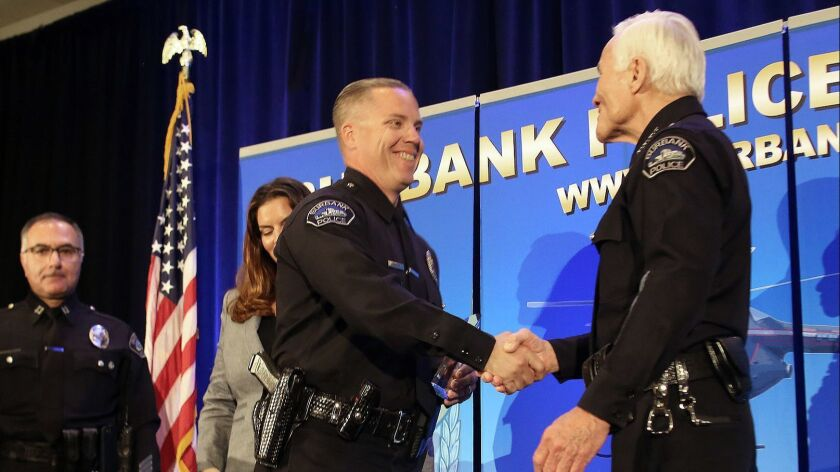 Burbank Police Officer John Embleton shakes hands with Burbank Police Chief Scott LaChasse as he is