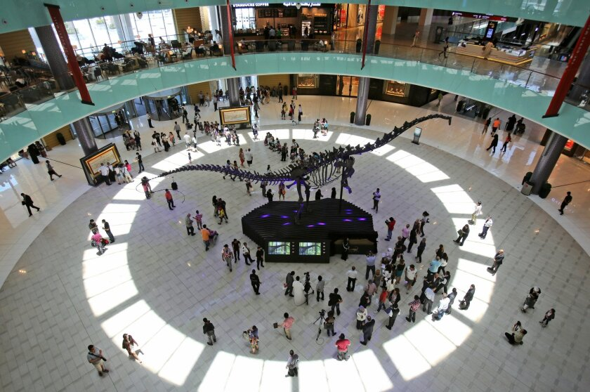 FILE - In this Monday, June 2, 2014 file photo, people visit a fossilized skeleton of a 155-million-year-old long-necked, whip-tailed adult sauropod dinosaur, at the Dubai Mall in Dubai, United Arab Emirates. Emaar Properties, the developer behind the Dubai Mall, one of the world's largest malls, and the Burj Khalifa, the world's tallest tower, said in a statement Sunday, Aug. 31, 2014 it will launch an initial public offering for part of its retail business in Dubai next month. The Dubai-based developer said in a statement that it expects to sell at least 15 percent of the company known as Emaar Malls Group in the offering. (AP Photo/Kamran Jebreili, File)