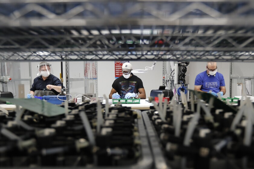 FILE - In this May 13, 2020, file photo, Ford Motor Co., line workers put together ventilators that the automaker is assembling at the Ford Rawsonville plant in Ypsilanti Township, Mich. American industry rebounded last month as factories began to reopen for the first time since being shut down by the coronavirus in Aprll. The Federal Reserve said Tuesday, June 16, 2020, that industrial production — including output at factories, mines and utilities — rose 1.4% in May after plummeting a record 12.4% in April and 4.6% in March. (AP Photo/Carlos Osorio, File)