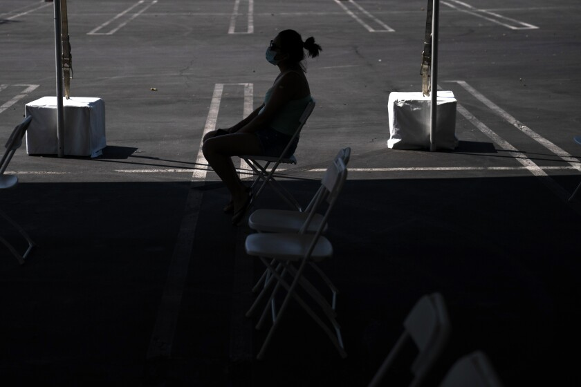FILE - In this Aug. 28, 2021, file photo, a woman waits in the holding area after receiving the COVID-19 vaccine at a clinic set up in the parking lot of CalOptima in Orange, Calif. California is seeing lower coronavirus transmission than other U.S. states as virus cases and hospitalizations decline following a summer surge. State health experts say relatively high vaccination rates ahead of the arrival of the delta variant made a difference. (AP Photo/Jae C. Hong, File)