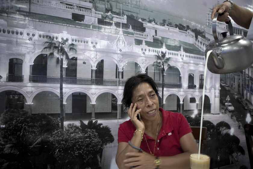 Regina Martinez talks on a cellphone at a restaurant.