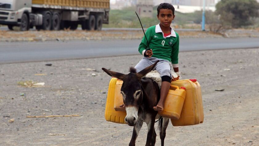 A Yemeni boy rides a donkey carrying plastic containers full of water in an impoverished coastal village on the outskirts of the Yemeni port city of Hudaydah last month.