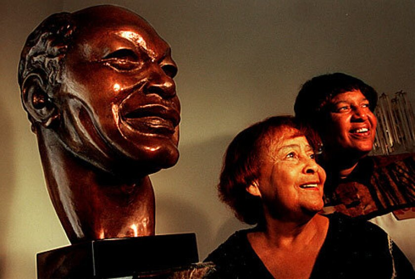 Ethel Bradley and her daughter Lorraine Bradley pose next to a bust of former Los Angeles Mayor Tom Bradley that the family donated to the African American Museum.