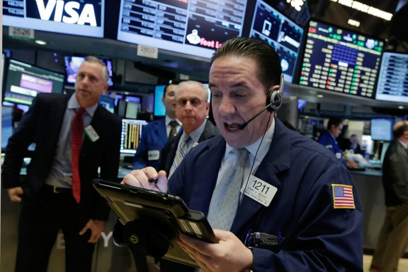Trader Tommy Kalikas right, works on the floor of the New York Stock Exchange, Monday, Nov. 23, 2015. Stocks are opening slightly lower as the market loses momentum after logging its biggest weekly gain of the year. (AP Photo/Richard Drew)