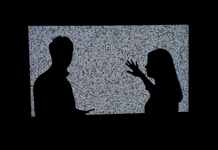 Silhouettes of two people in front of a work of art.