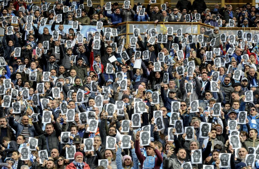 Napoli supporters hold up prints of Napoli defender Kalidou Koulibaly's portrait in his support ahead of a Serie A soccer match between Napoli and Carpi, at the San Paolo stadium in Naples, Italy, Sunday, Feb. 7, 2016. Last week during the team's game against Lazio the match was suspended for four