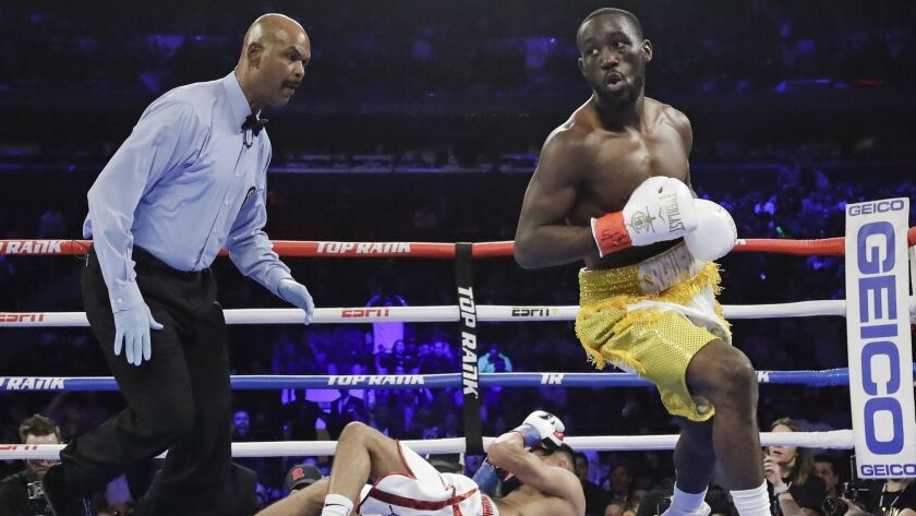 Terence Crawford, right, reacts after knocking down England's Amir Khan during the first round of a