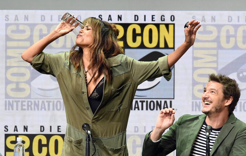 Actor Halle Berry takes a drink at a Comic-Con panel.