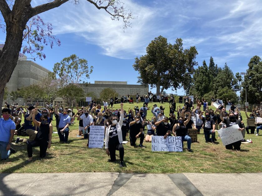 Hundreds kneel near the O.C. Sheriff's headquarters to protest police brutality.