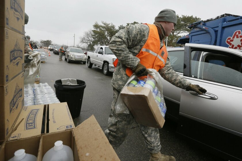Members of the Michigan National Guard load bottled water for residents at a fire station, Thursday, Jan. 28, 2016 in Flint, Mich. The Michigan Legislature voted Thursday to direct another $28 million to address Flint's water emergency, allocating money for bottled water, medical assessments and ot