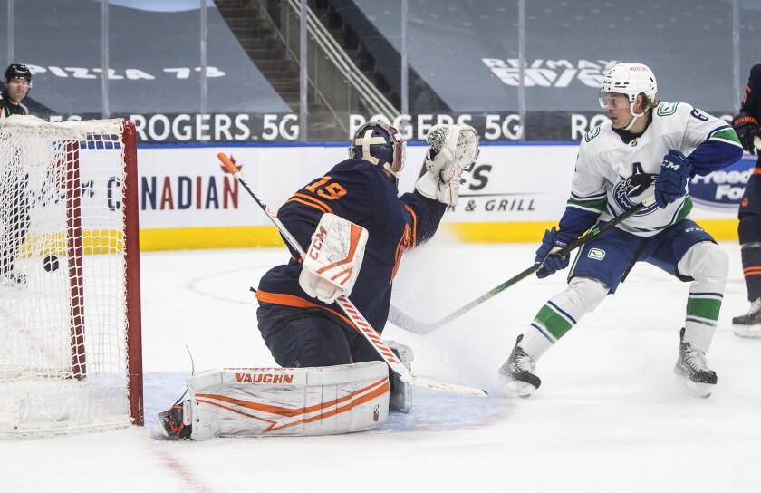 Edmonton Oilers goalie Mikko Koskinen (19) is scored against by Vancouver Canucks' Brock Boeser (6) during third-period NHL hockey game action in Edmonton, Alberta, Saturday, May 15, 2021. (Jason Franson/The Canadian Press via AP)