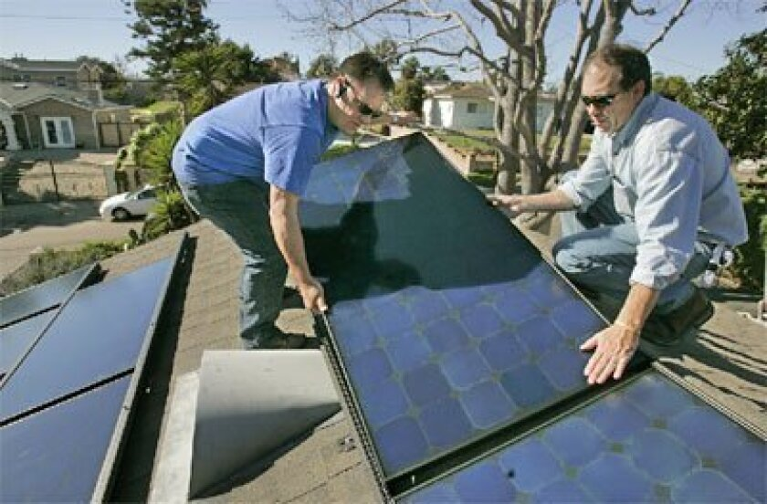 Joe Bartolomei (left) and Lee Sterling of Solartistry Inc. installed solar panels on a home on Del Rio Avenue in Encinitas yesterday. Encinitas has proposed creating a long-term payment plan for solar power systems. (Charlie Neuman / Union-Tribune)