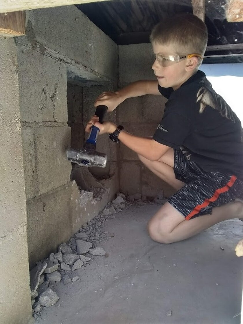 Davy, 8, knocking down the kennel cinder blocks to make room to install roost bars for the chickens.