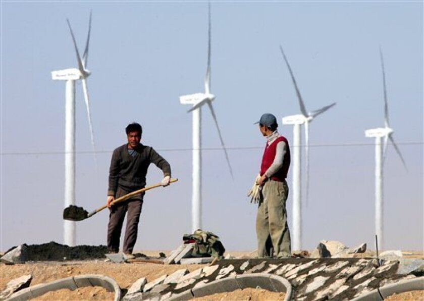 In this Oct. 12, 2005 file photo, workers build a highway near a wind farm in the Gobi desert, in China's northwest Gansu province. Global investments in renewable energy jumped by 32 percent to $211 billion last year, boosted by wind farm development in China and rooftop solar panels in Europe, U.N. officials said Thursday July 7 2011. A report by the U.N. Environment Program shows that solar, wind, biomass and other forms of green energy are gaining momentum, despite the lack of progress in international climate talks aimed at slowing emissions of heat-trapping gases from fossil fuels. (AP Photo/Greg Baker, File)