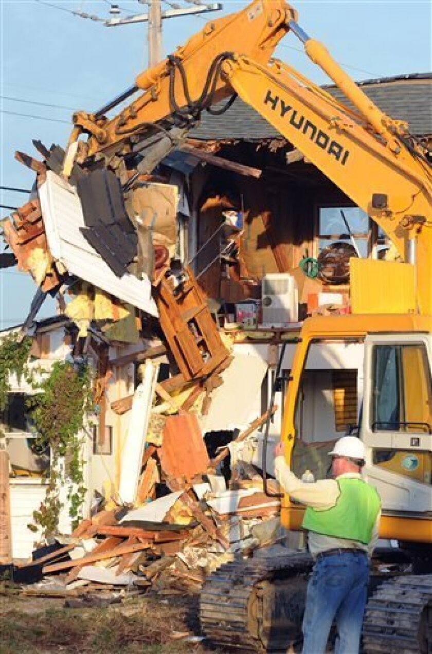 The property formerly owned by Dr. Earl Bradley is demolished in Lewes, Del., Monday, Oct. 10, 2011. Crews have begun demolishing a doctor's office in Delaware where pediatrician Earl Bradley sexually abused scores of young patients over more than a decade. (AP Photo/The News Journal, Gary Emeigh)