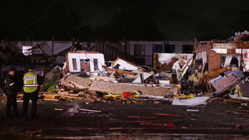 Police stand at the ruins of a hotel in El Reno, Okla., Sunday, May 26, 2019, following a likely tor
