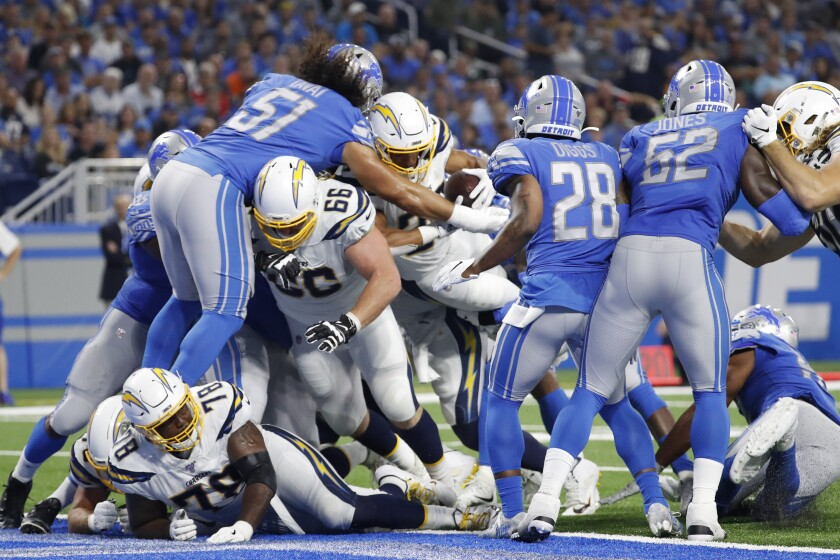 Chargers running back Austin Ekeler (30) fumbles the ball against the Detroit Lions in the second half of Sunday's game at Ford Field.