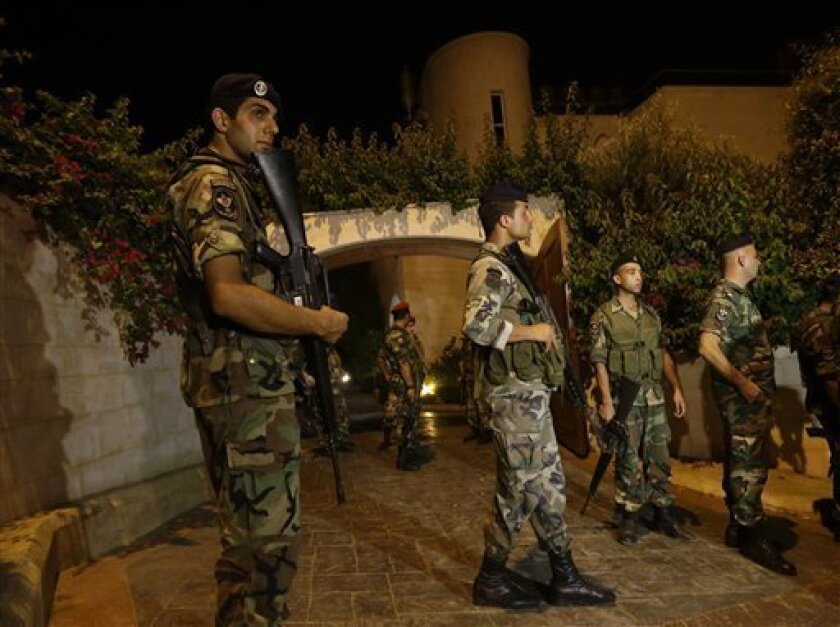 Lebanese army soldiers stand guard at the entrance to a villa where a rocket attack few meters away from one of the entrances to the Lebanese presidential palace, in Fayadiyyeh area, eastern Beirut, Lebanon, early Friday, Aug. 2, 2013. At least two rockets slammed Thursday night into an area south of the Lebanese capital that houses the Defense Ministry and presidential palace, Lebanon's state-run news agency said. The attack comes on the same day when President Michel Suleiman gave a speech on