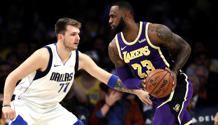 Los Angeles Lakers' LeBron James (23) is defended by Dallas Mavericks' Luka Doncic (77) during the f