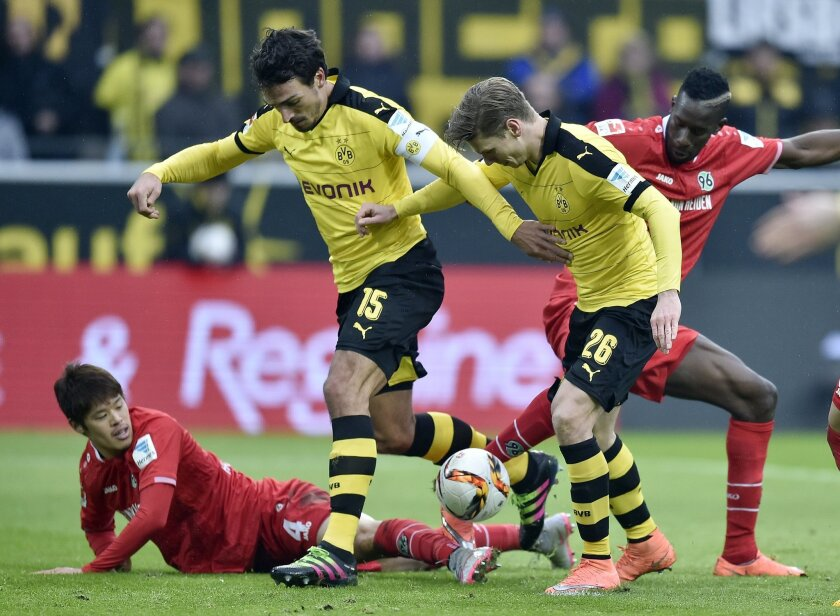 Dortmund's Mats Hummels and Dortmund's Lukasz Piszczek, center challenge for the ball with Hannover's Hiroki Sakai, left, and Hannover's Salif Sane, right, during the German Bundesliga soccer match between Borussia Dortmund and Hannover 96  in Dortmund, Germany, Saturday, Feb. 13, 2016. (AP Photo/M