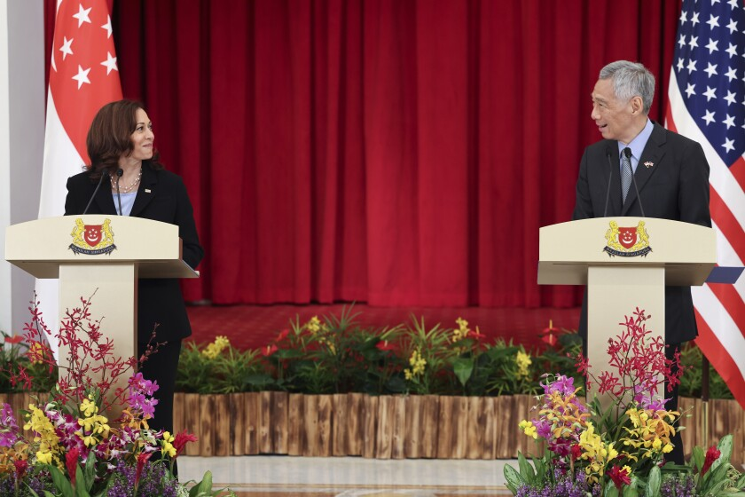 U.S. Vice President Kamala Harris and Singapore Prime Minister Lee Hsien Loong look at each other while standing