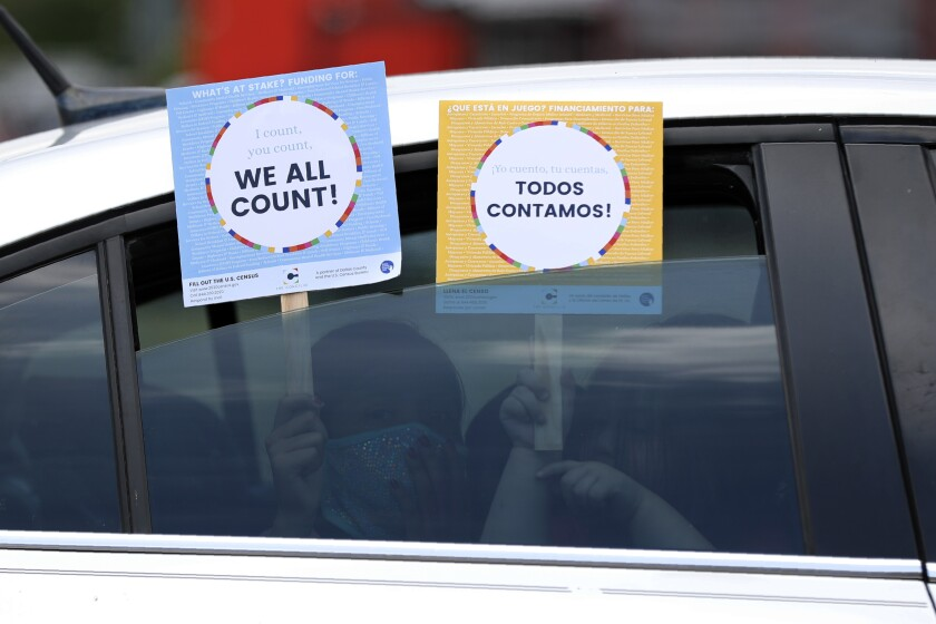 Two young children hold signs through the car window that make reference to the 2020 U.S. Census as they wait in the car with their family at an outreach event in Dallas, Thursday, June 25, 2020. In a collaborative effort, the nonprofit group, The Concilio, partnered with the North Texas Food Bank, Catholic Charities Dallas and Bachman Lake Together, to hold the event where area residents were encouraged to report their family numbers to the U.S. Census. The outreach event was held in the Bachman Lake community which historically is one of many undercounted neighborhoods in Dallas County according to The Concilio. Due to COVID-19, the Census self-respond date online, by phone or mail has been extended to Oct. 31. (AP Photo/Tony Gutierrez)
