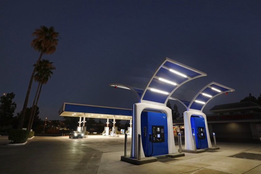Two futuristic-looking fuel pumps are shown at a refueling station.