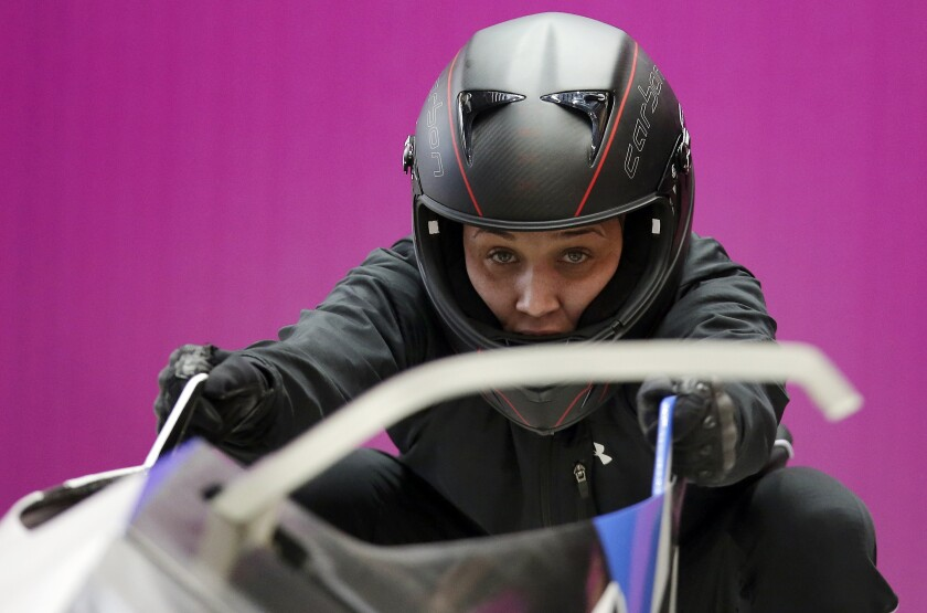 FILE - In this Sunday, Feb. 16, 2014, file photo, breakman Lolo Jones, of the United States, prepares for a training session with her teammate Jazmine Fenlator for the women's bobsleigh at the 2014 Winter Olympics, in Krasnaya Polyana, Russia. Jones hasn't returned to China since 2008, since one bad step in what was then the biggest race of her life cost her an Olympic gold medal. Her stance might change in 2022. (AP Photo/Michael Sohn, File)