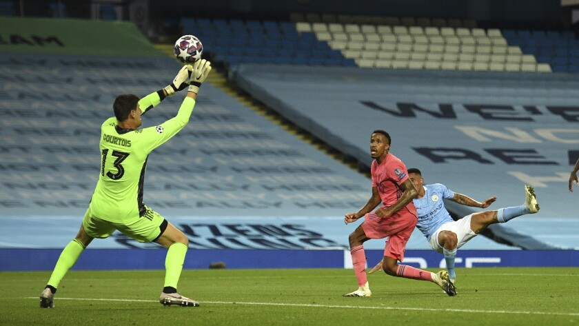 Real Madrid's goalkeeper Thibaut Courtois saves a shot by Manchester City's Gabriel Jesus during the Champions League, round of 16, second leg soccer match between Manchester City and Real Madrid at the Etihad Stadium in Manchester, England, Friday, Aug. 7, 2020. (Oli Scarff/Pool Photo via AP)