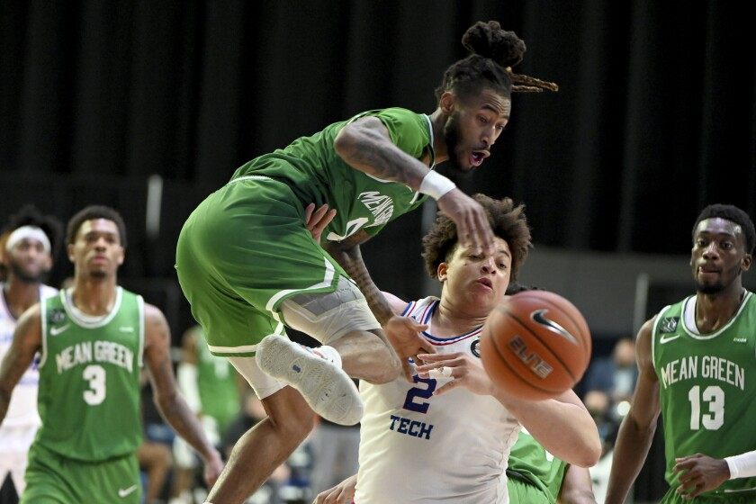 North Texas guard James Reese (0) goes after the ball with Louisiana Tech forward Kenneth Lofton Jr. (2) in the second half of an NCAA college basketball game in the Conference USA men's tournament, in Frisco, Texas, Friday, March 12, 2021. (AP Photo/Matt Strasen)