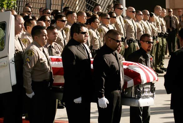 The casket of Los Angeles County Sheriff's Deputy Juan Abel Escalante is removed from the hearse for funeral services at the Cathedral of Our Lady of the Angels in Los Angeles. Escalante, who was assigned to the county's Men's Central Jail in downtown and guarded some of the region's most dangerous inmates, was not wearing a uniform but was on his way to work when he was shot and killed.